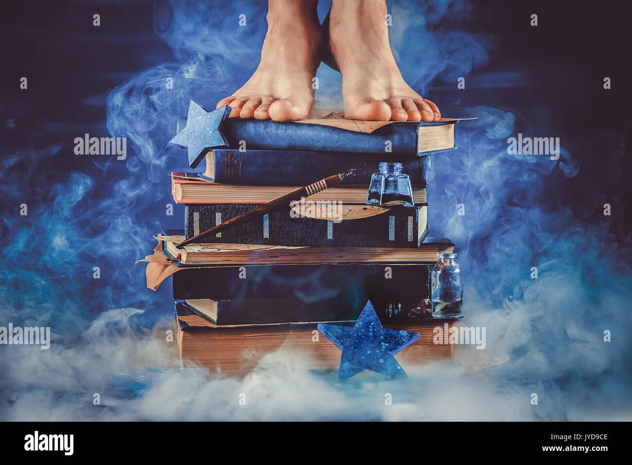 Kid pie sobre un montón de libros en el medio de una nube de humo oscuro bodegón en tonos de azul. educación la metáfora. Imagen De Stock