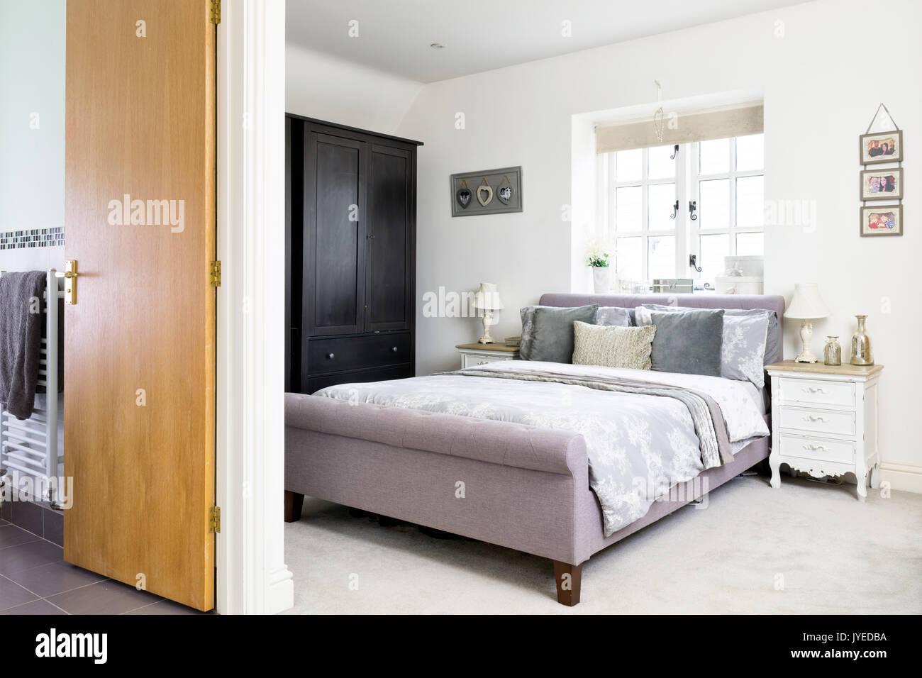 Una cama tamaño king en un moderno dormitorio doble con baño. Imagen De Stock