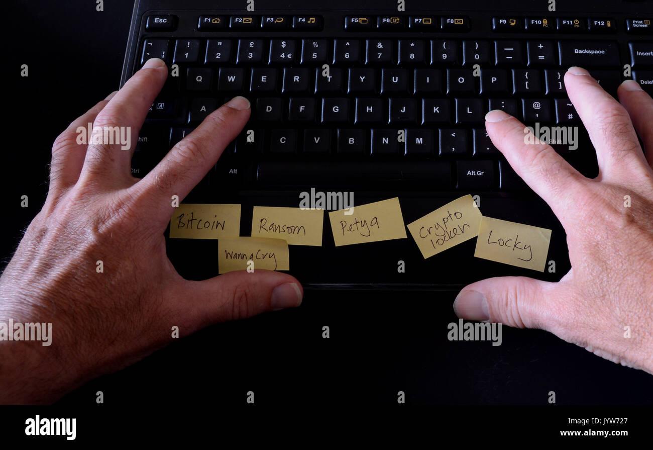 Hombre escribiendo en el teclado del ordenador con post-it notes en representar nombres ransomware Imagen De Stock