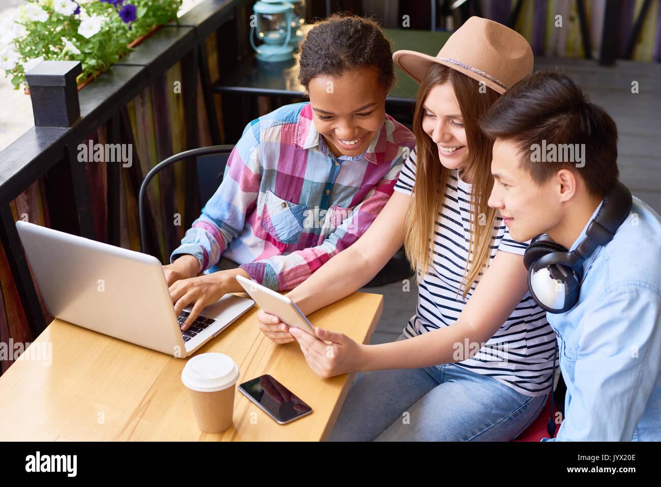 Amigos utilizando dispositivos digitales de Cafe Imagen De Stock
