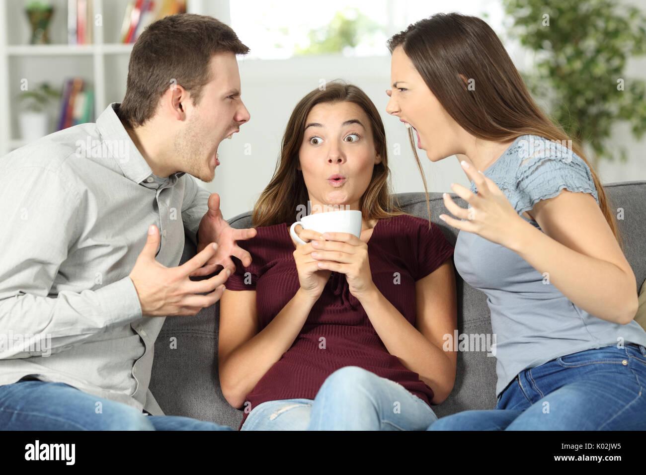 Malestar amigo en medio de una pareja discusión en casa Foto de stock