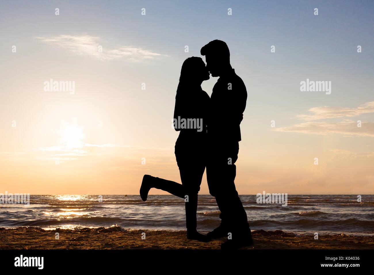 Silueta De Pareja Enamorada De Pie A Orillas Del Mar Al Atardecer