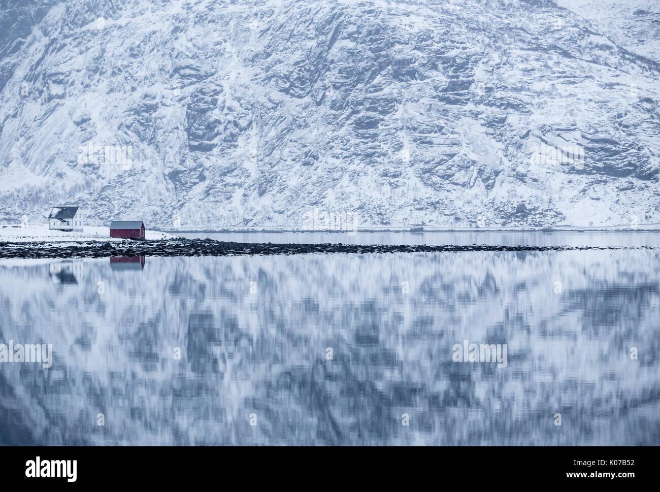 Reflejo perfecto de las montañas y la casa roja, Islas Lofoten, Noruega Foto de stock