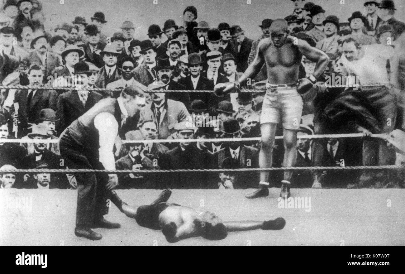 """Jack Johnson (1878-1946), apodado """"El Gigante de Galveston, Afro-americano campeón del mundo de boxeo, 1908-1915, situándose en las cuerdas en un combate de boxeo con un opositor no identificado, quien parece haber sido eliminado. circa 1910 Foto de stock"""