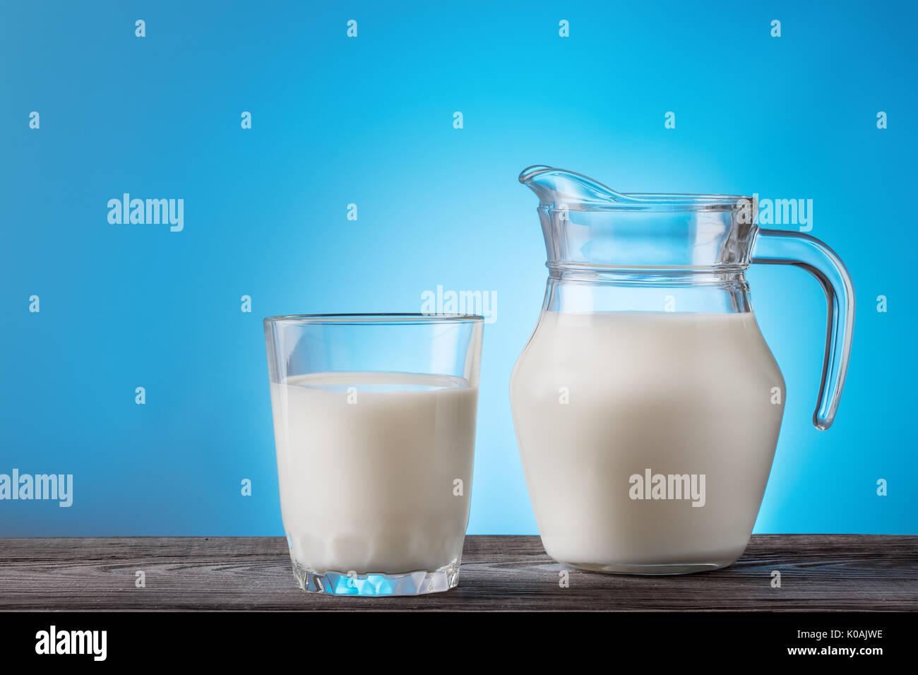 La leche en un vaso y jarra sobre una mesa de madera Imagen De Stock
