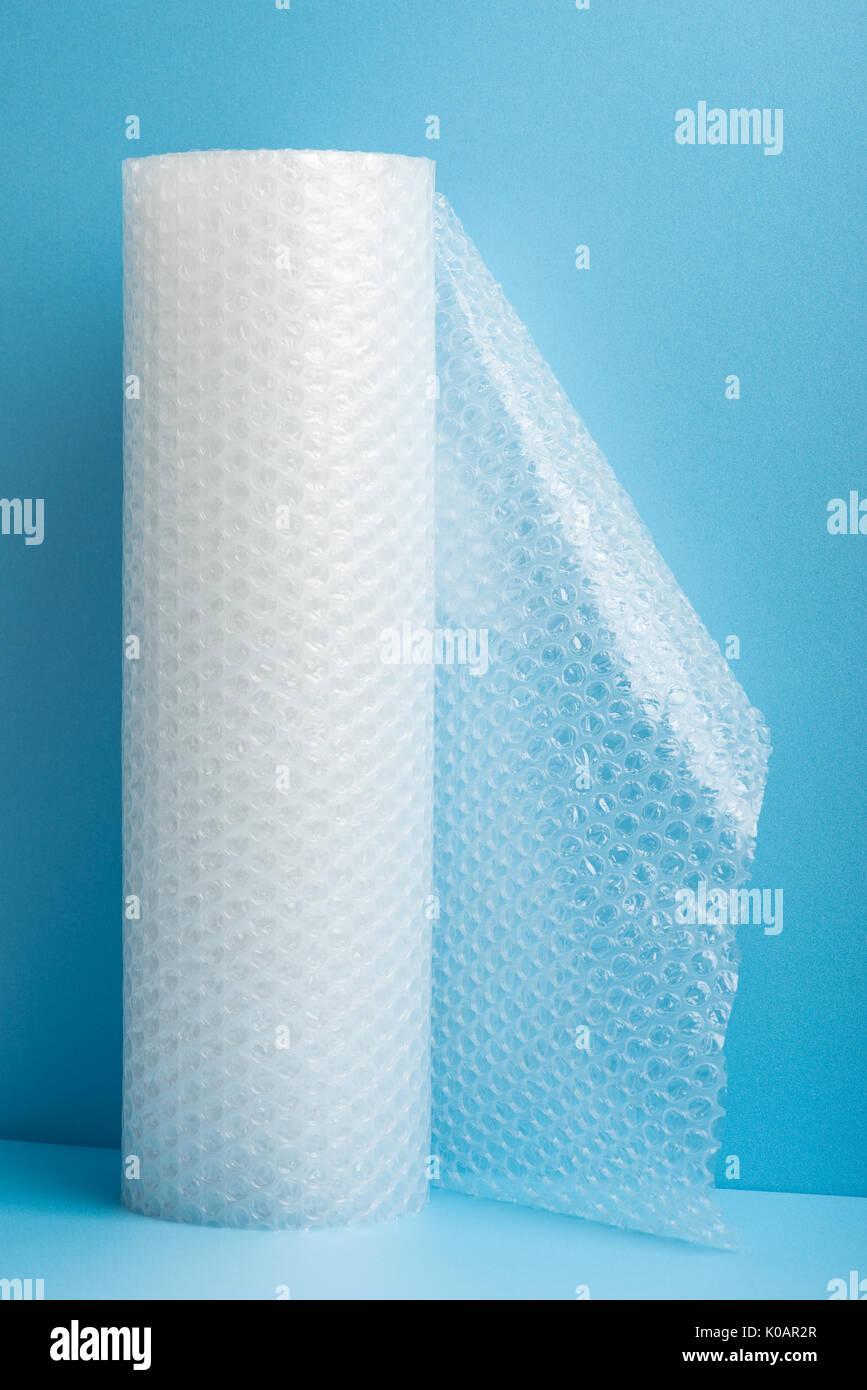 Rollo de envoltura de burbujas sobre fondo azul. Imagen De Stock