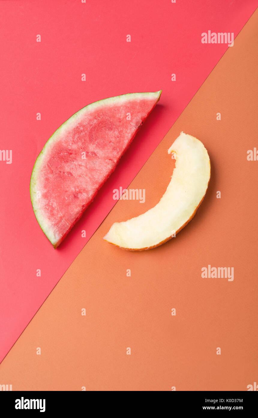 La rebanada de sandía con piedras sobre fondo rojo y melón aislado sobre fondo naranja Imagen De Stock