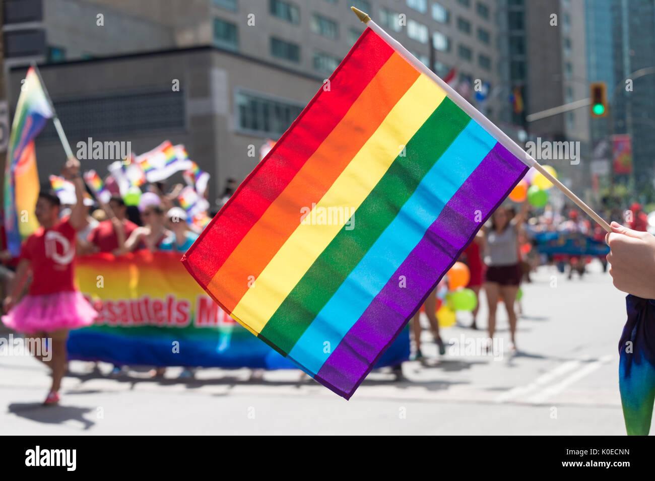 Montreal, Canadá - 20 de agosto de 2017: Gay la bandera del arco iris en Montreal desfile del orgullo gay con participantes borrosa en el fondo Imagen De Stock