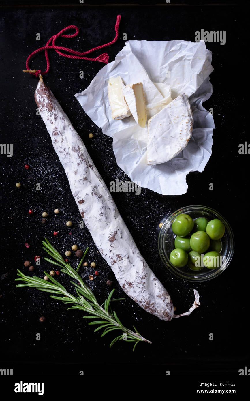 Fuet embutido con queso y aceitunas. Aperitivo español sobre fondo negro. Vista desde arriba. Imagen De Stock