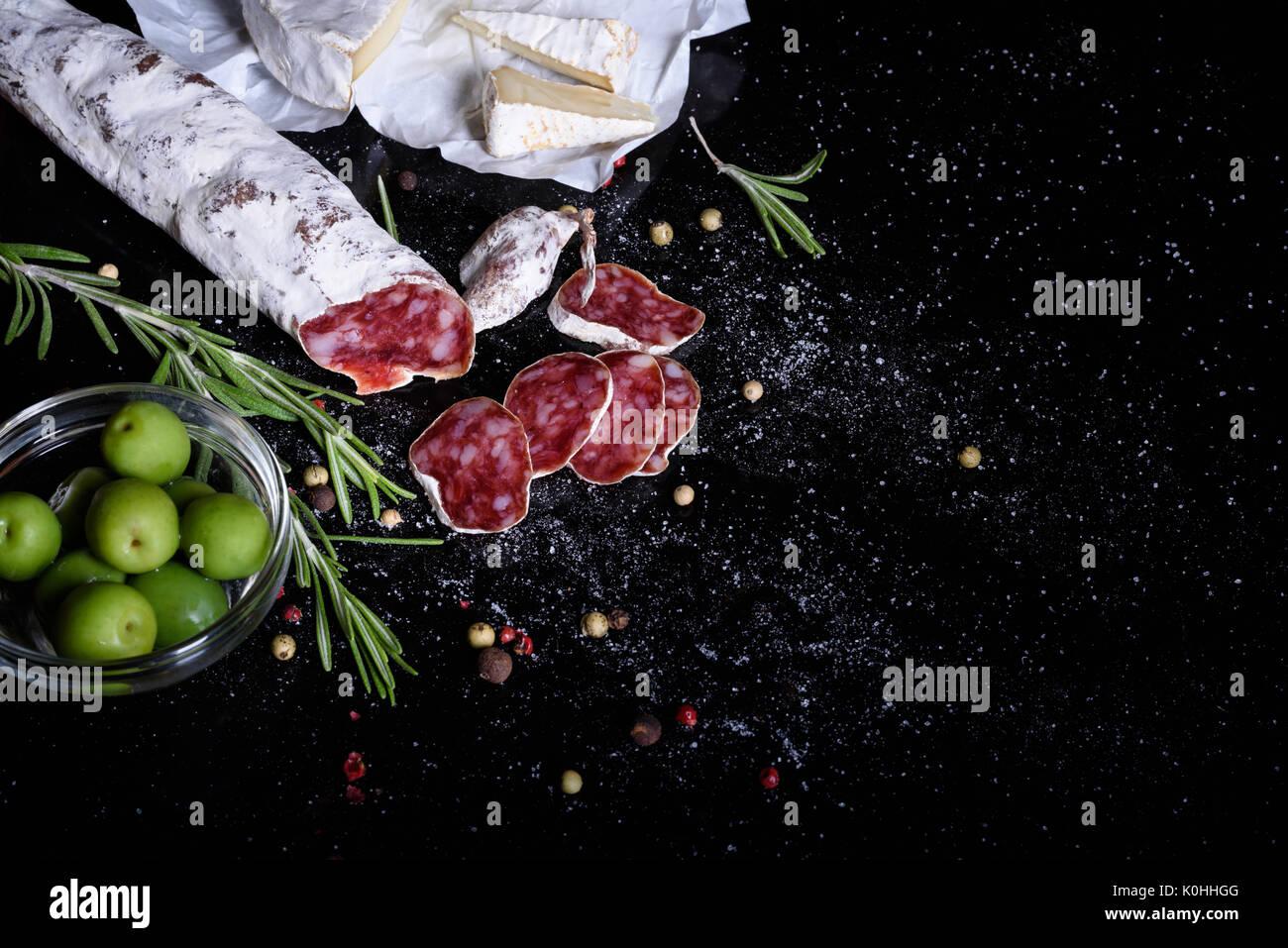 Aperitivo tradicional española sobre fondo negro. Fuet embutido con queso y aceitunas. Vista desde arriba. Imagen De Stock