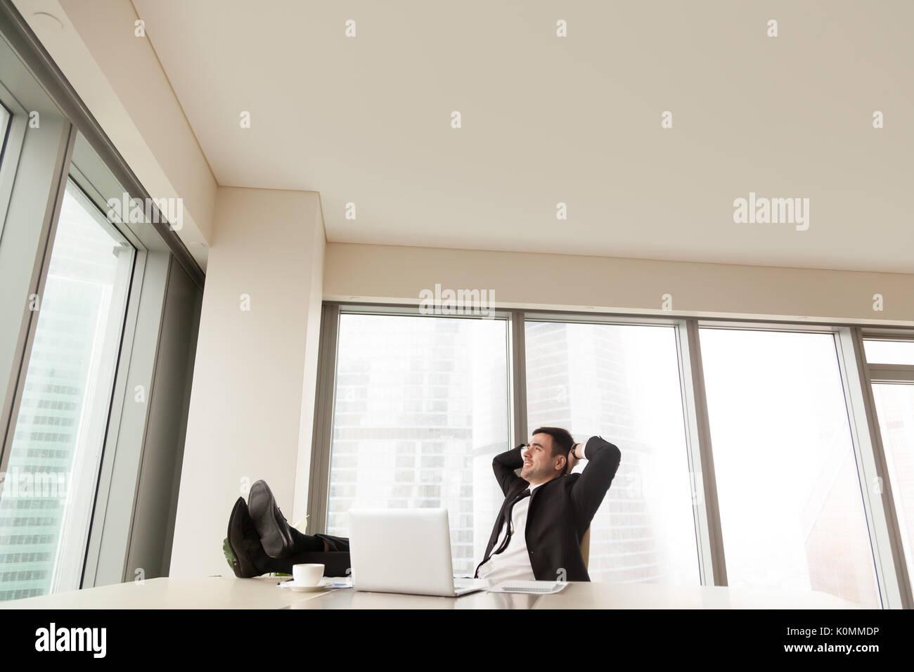 Empresario relajante en la oficina con los pies hacia arriba en el escritorio, copyspace Imagen De Stock