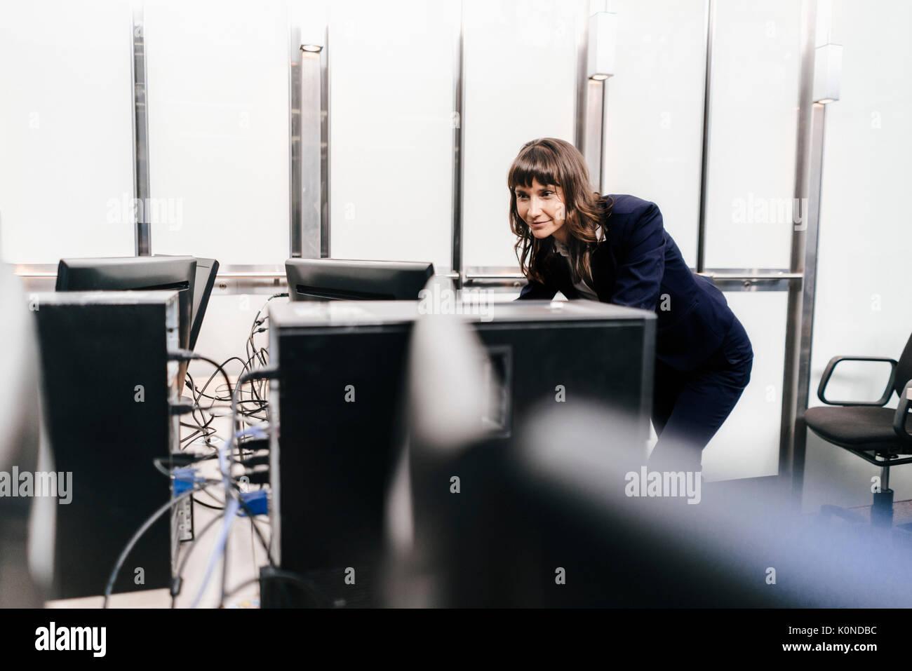 Exitosa empresaria mirando monitores en Office Imagen De Stock