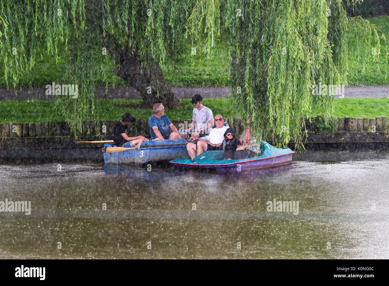 Los turistas en un lago con botes, refugiarse bajo un árbol de sauce desde un aguacero torrencial. Imagen De Stock