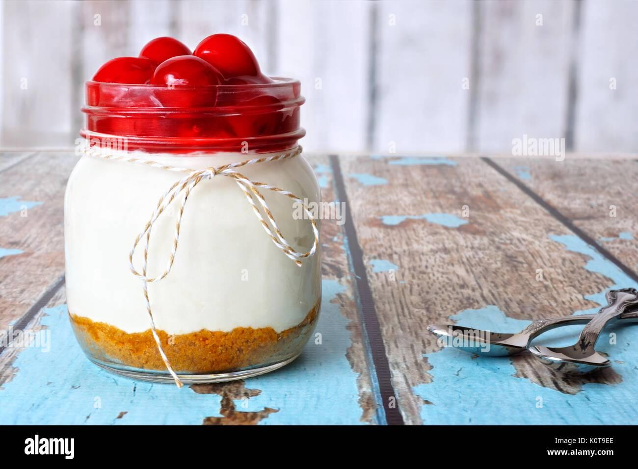 Cheesecake de cerezas dulces en una jarra de albañil sobre un fondo de madera rústica Imagen De Stock
