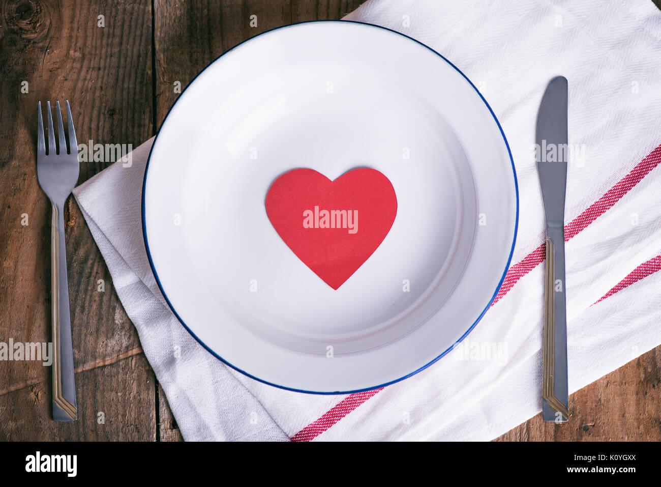 Concepto de dieta y pérdida de peso. Vaciar la placa con papel rojo corazón en medio de la placa. Foto de stock