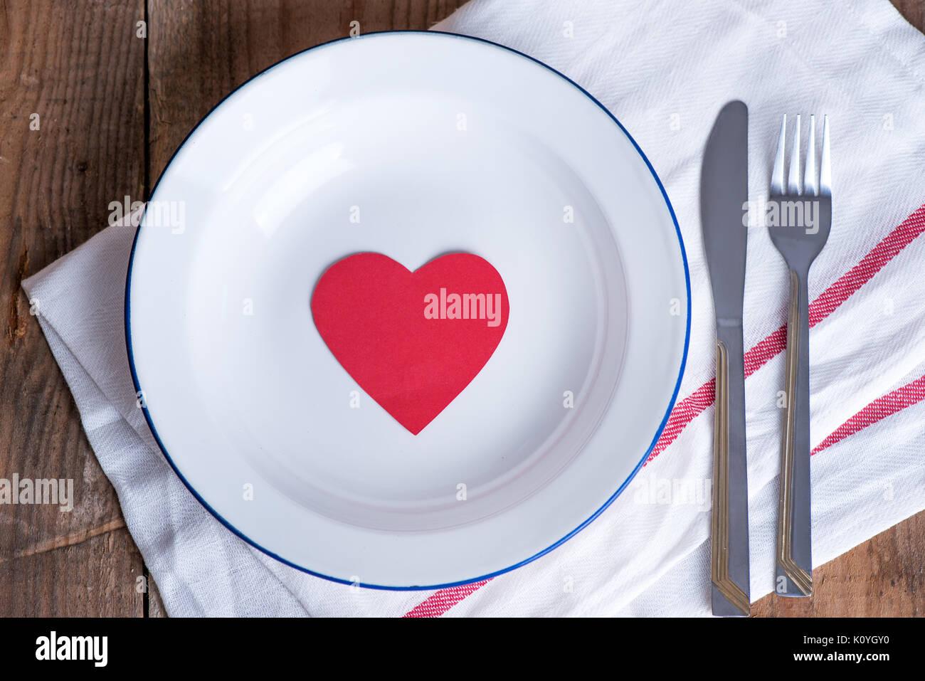 Concepto de dieta y pérdida de peso. Vaciar la placa con papel rojo corazón en medio de la placa. Imagen De Stock