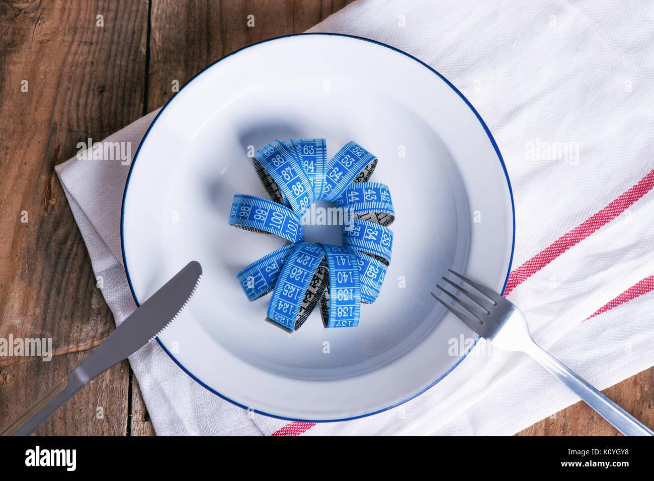 Concepto de dieta y pérdida de peso. Placa de vacío con cinta métrica en el centro de la placa. Imagen De Stock