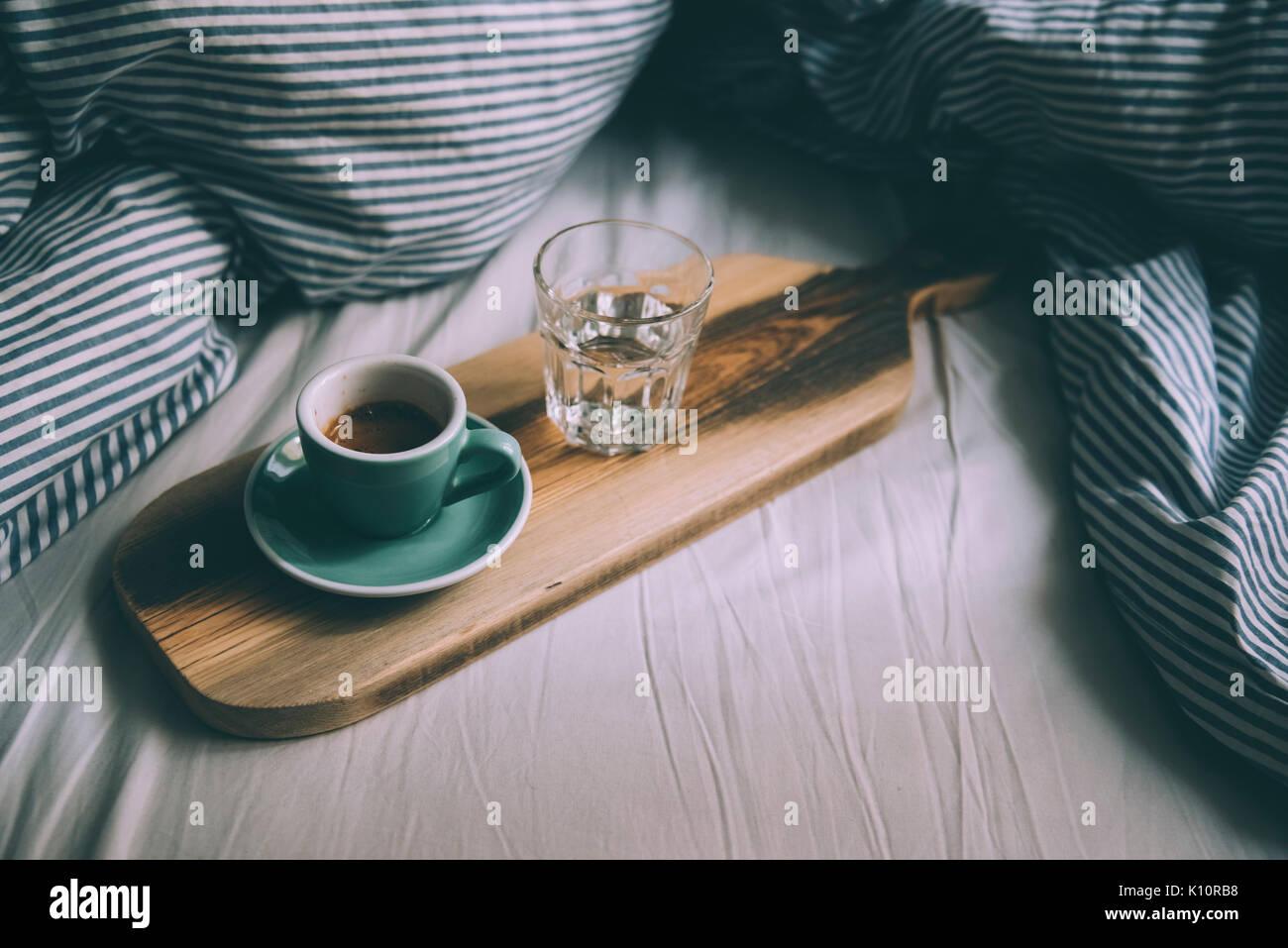 Hermosa mañana trabajando en la cama essentials: portátil y una fresca mañana café con crema tigre hermoso en un rústico de madera hechos a mano en bandeja Imagen De Stock