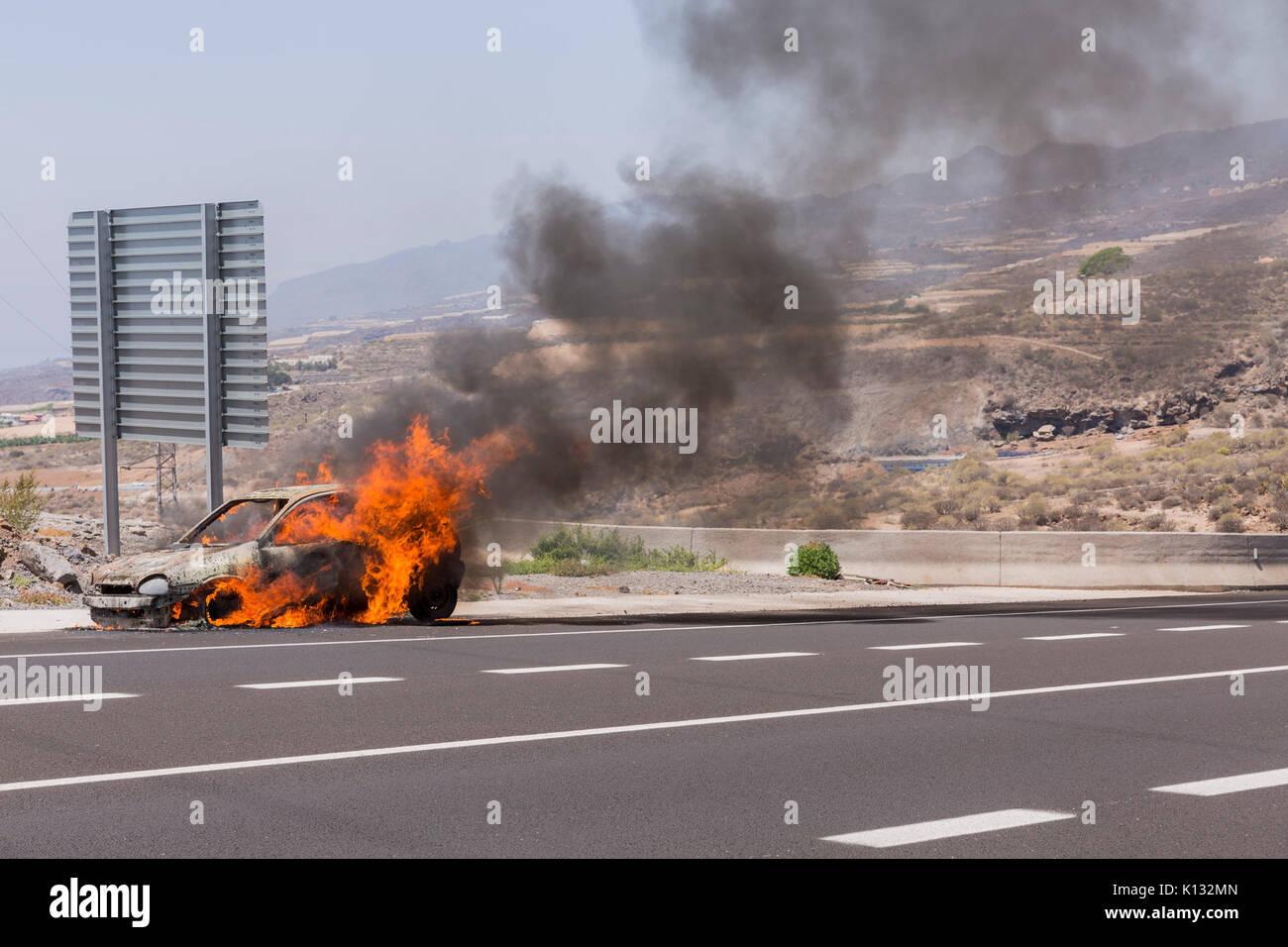 Opel Corsa en llamas a la vera del camino Imagen De Stock