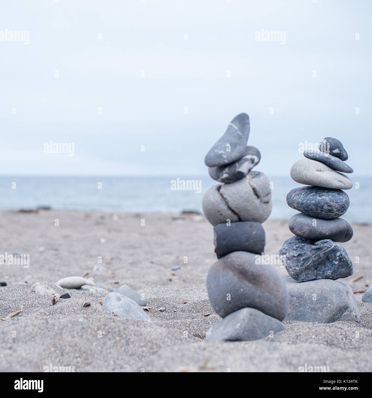 Monocromo Azul, sereno, rocas apiladas en una playa de California que simbolizan la paz, equilibrio, meditación Foto de stock