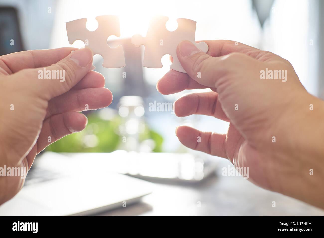 Joven empresario intentando conectar par pieza del puzzle con sun flare y fondo desenfocado,el símbolo de asociación y conexión. La estrategia de negocio. Imagen De Stock
