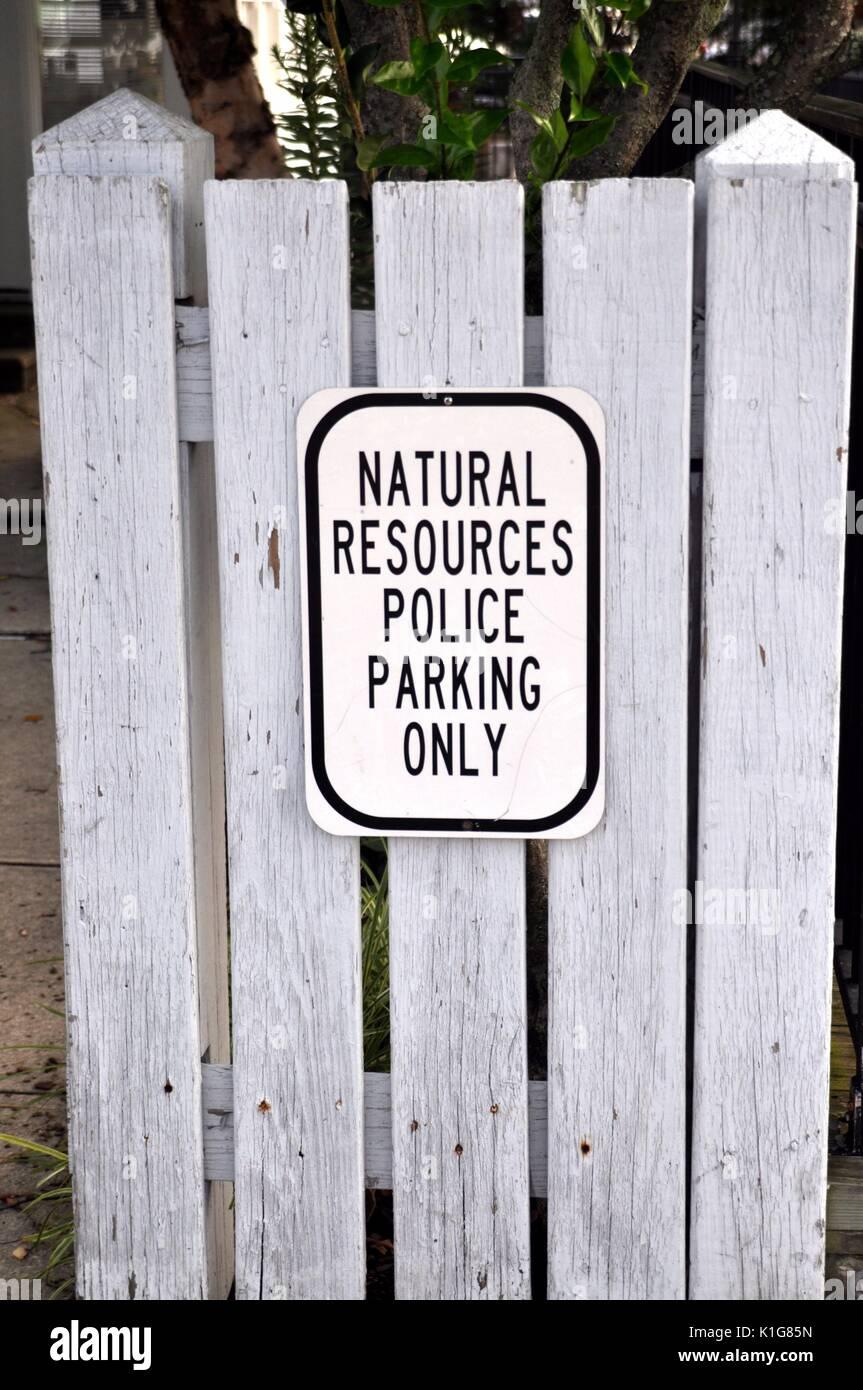 En blanco y negro de los recursos naturales sólo aparcamiento policía signo contra una valla gris. Imagen De Stock