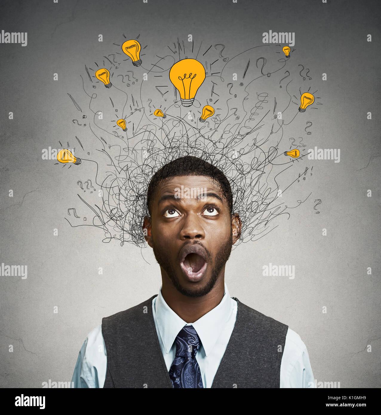 Joven con muchas bombillas de idea sobre la cabeza mirando hacia arriba aislado sobre la pared gris de fondo. Imagen De Stock