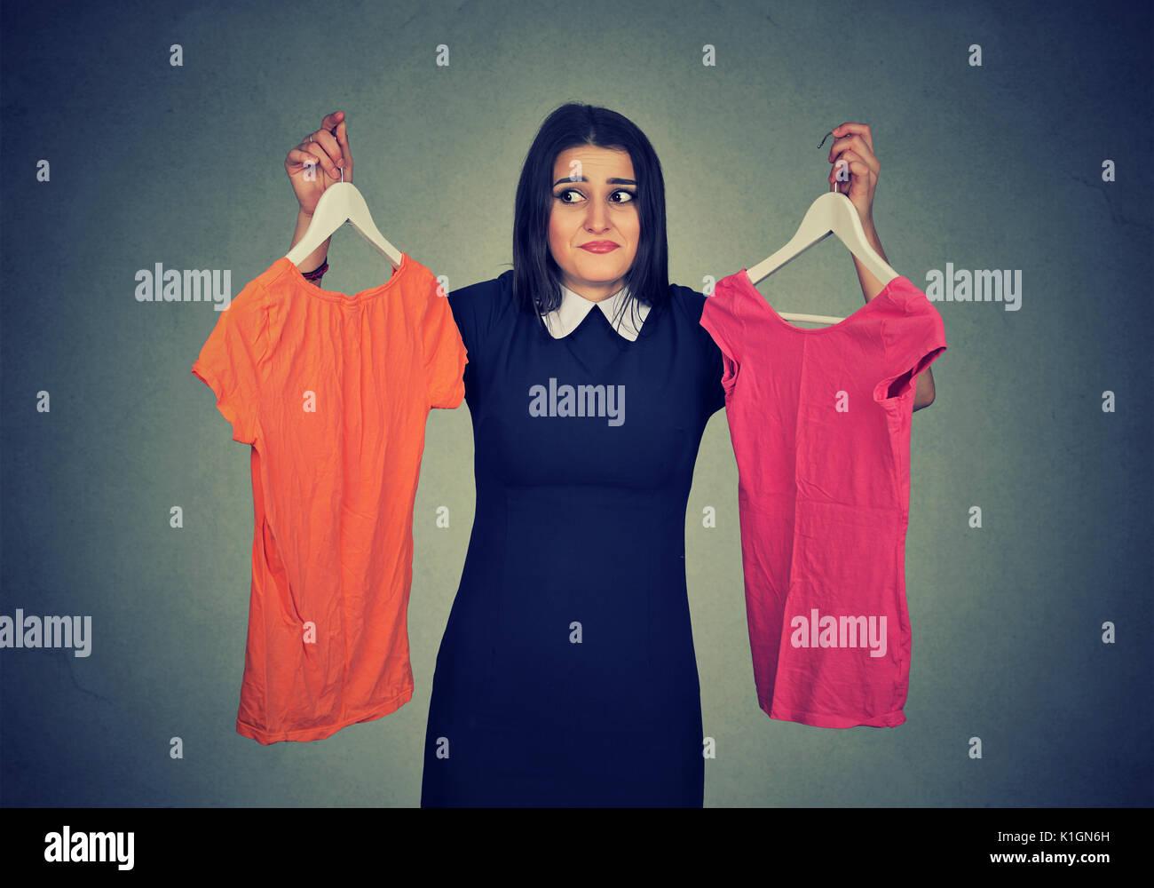 Confundirse mujer elegir entre vestidos y no puede hacer la decisión. Foto de stock