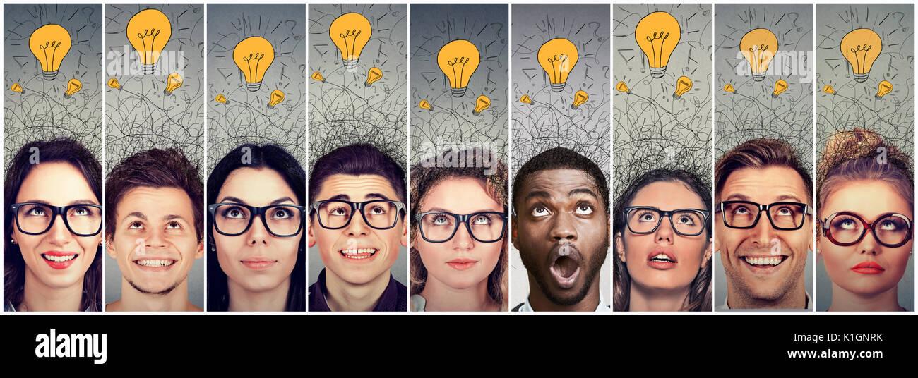 Grupo de jóvenes, hombres y mujeres con bombillas de luz muchas ideas sobre la cabeza mirando hacia arriba. Imagen De Stock