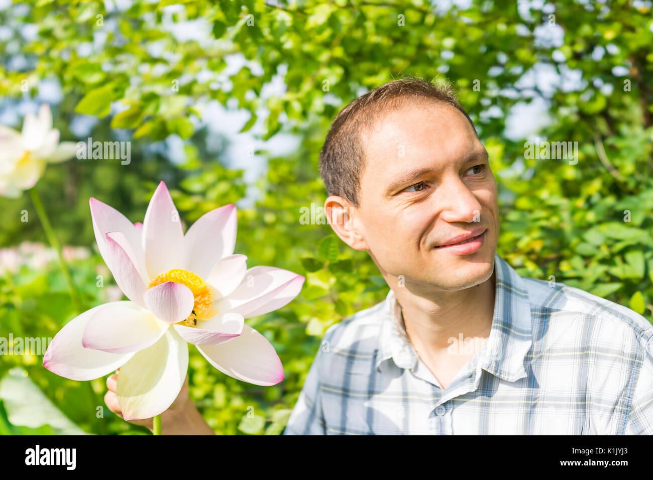 Closeup retrato de joven sonriente sosteniendo brillante blanco y rosa flor de loto con vaina de color amarillo en el interior Imagen De Stock