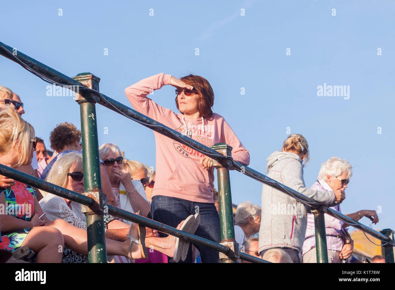 Una mujer iguales en la distancia con su mano para proteger sus ojos. Imagen De Stock