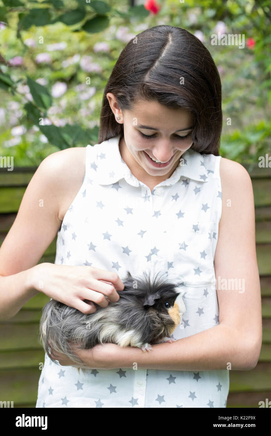 Chica en el jardín mirando después de cobayo Pet Imagen De Stock