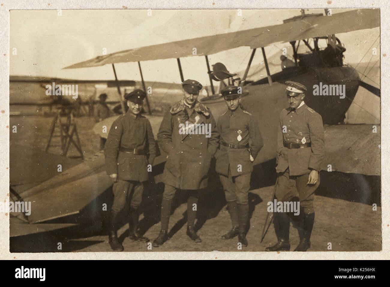 Cuatro pilotos alemanes delante de biplano Foto de stock