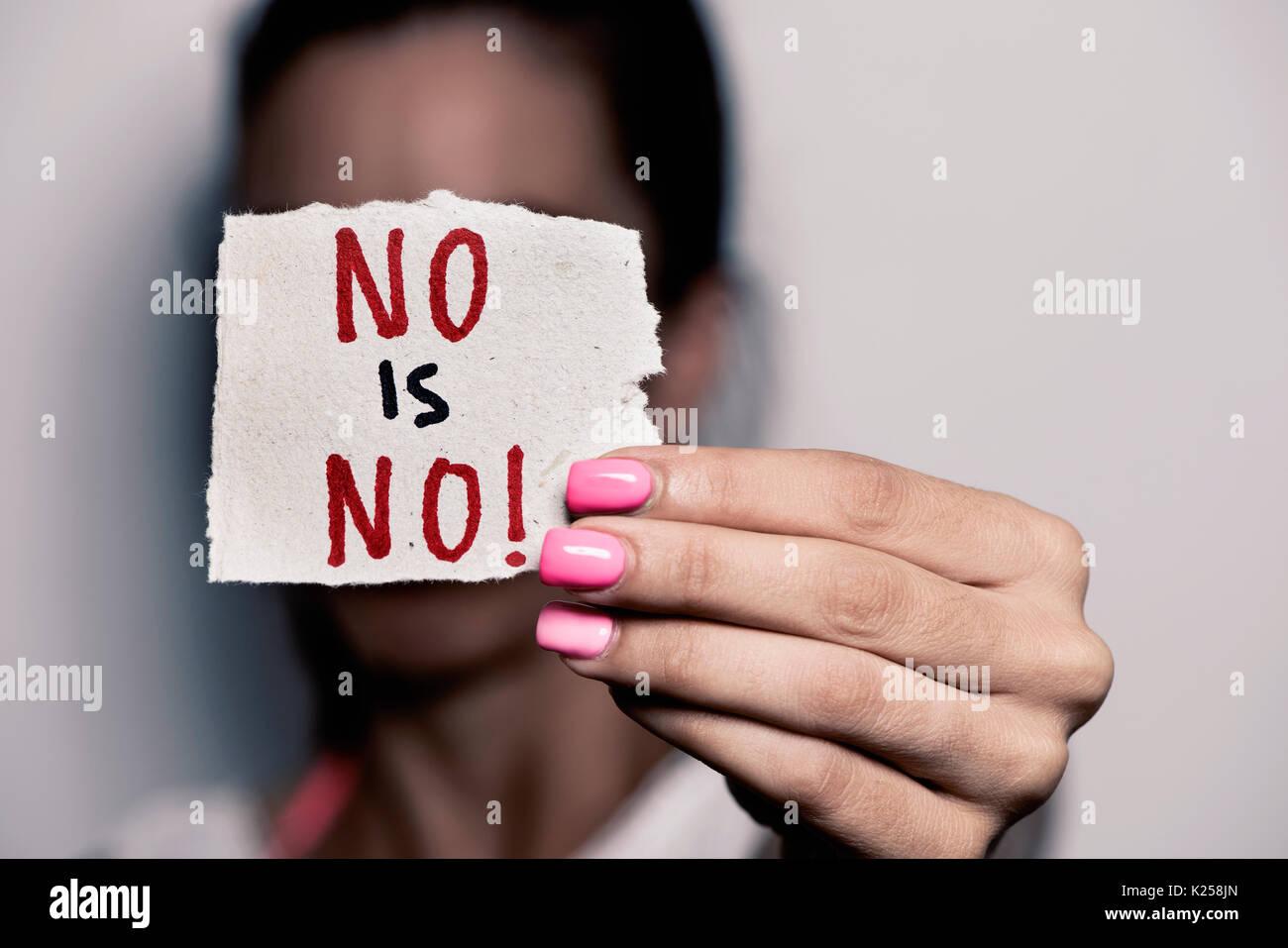 Primer plano de una joven mujer caucásica con clavos pulidos rosa sosteniendo un pedazo de papel con el texto no hay escrito en él, de delante de su rostro Imagen De Stock