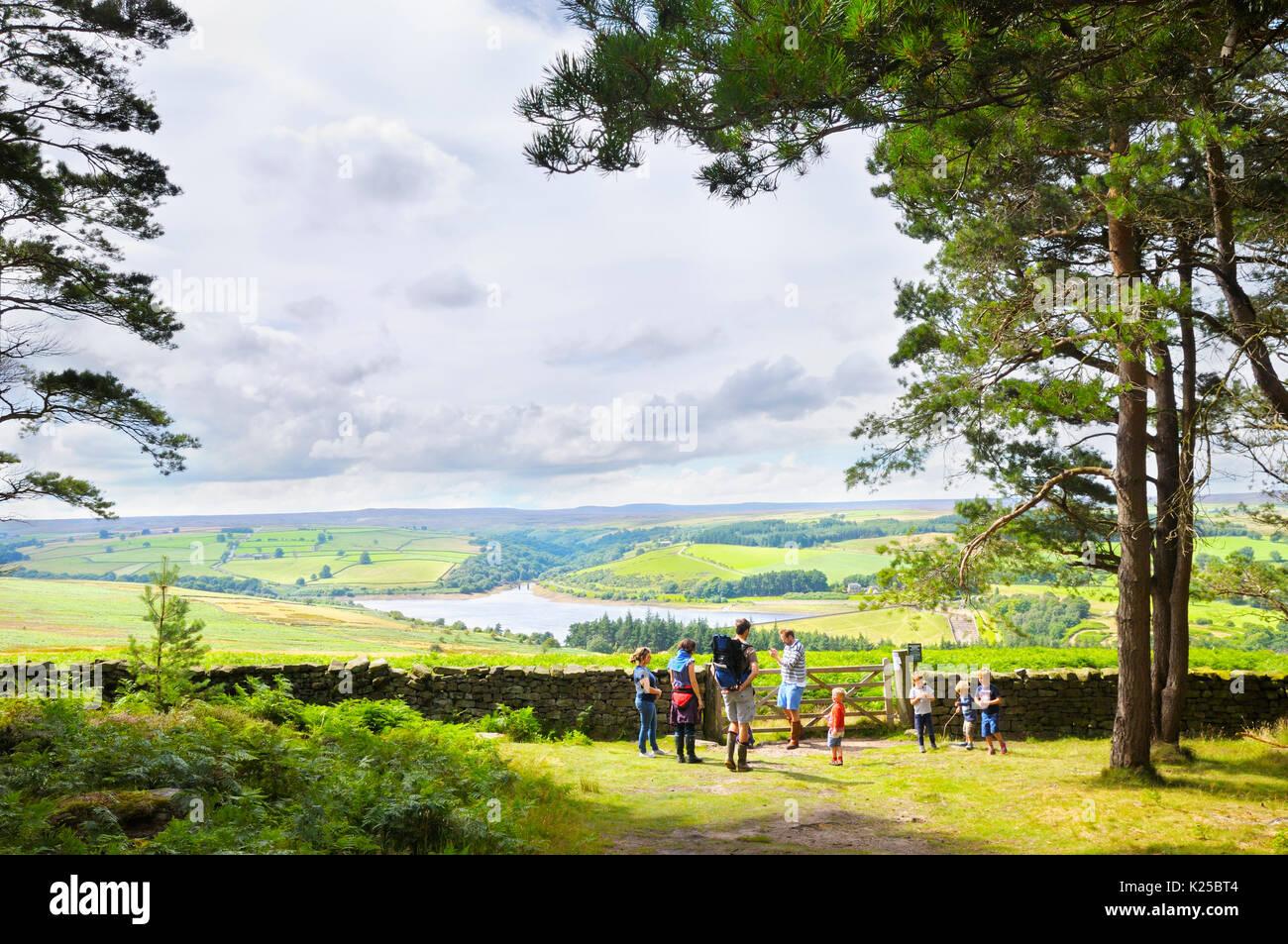 Las familias en un paseo por el bosque siguiendo una pausa de descanso para disfrutar de las vistas de la campiña de Yorkshire en torno a Leighton depósito, Ilton, North Yorkshire, Reino Unido Imagen De Stock