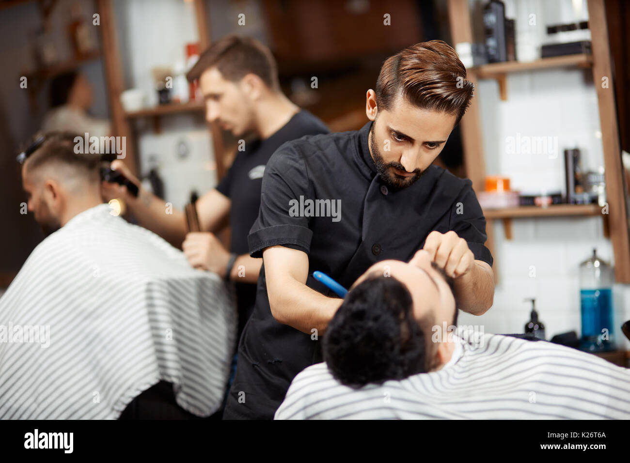 Peluquería en negro cortando el pan para brunet hombre. Foto de stock