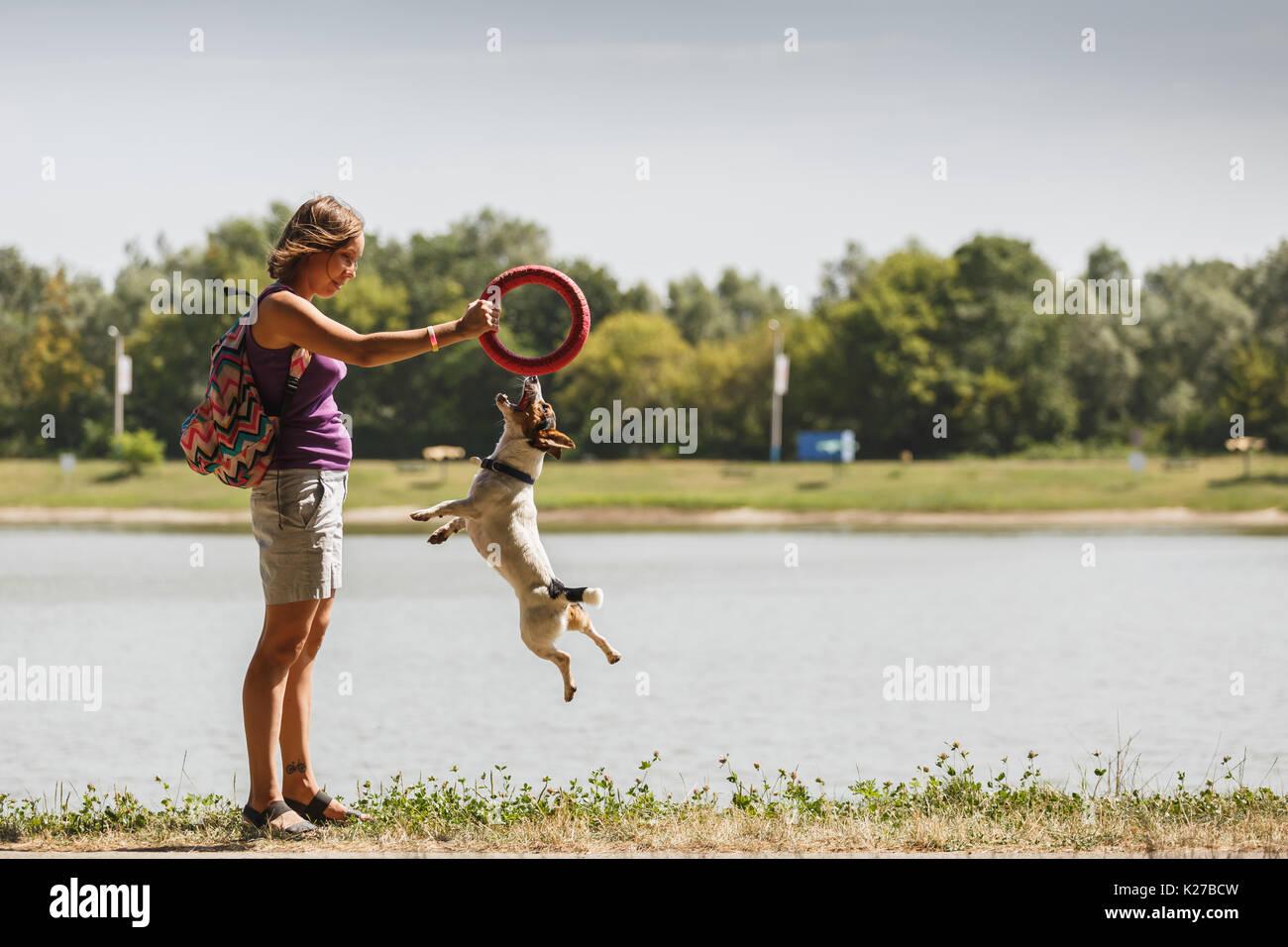 Mujer jugando con el perro en la naturaleza Imagen De Stock
