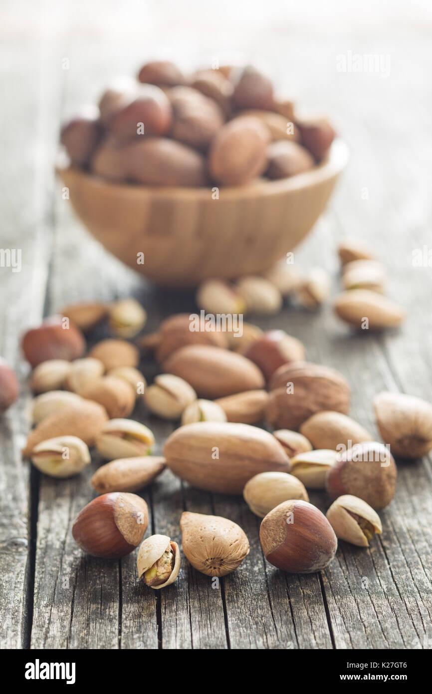 Los diferentes tipos de frutos secos en la cáscara de nuez. Las avellanas, nueces, almendras, nueces de nogal y los pistachos en la mesa de madera antigua. Imagen De Stock