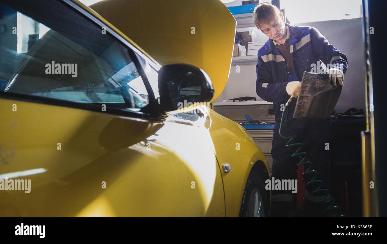 Mecánico de automóviles sopla el filtro de aire del automóvil en servicio Foto de stock