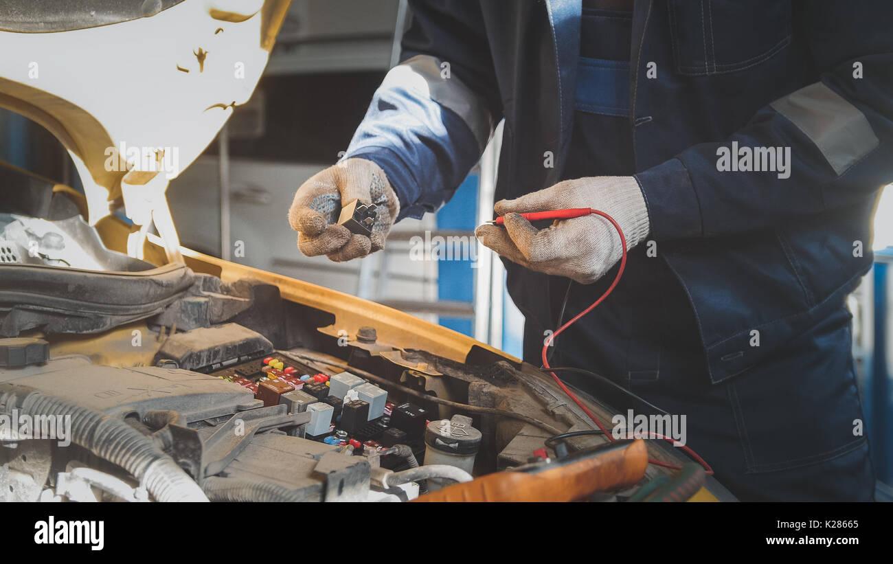 Mecánico en auto taller trabaja con coche eléctrico - cableado eléctrico, voltímetro Imagen De Stock