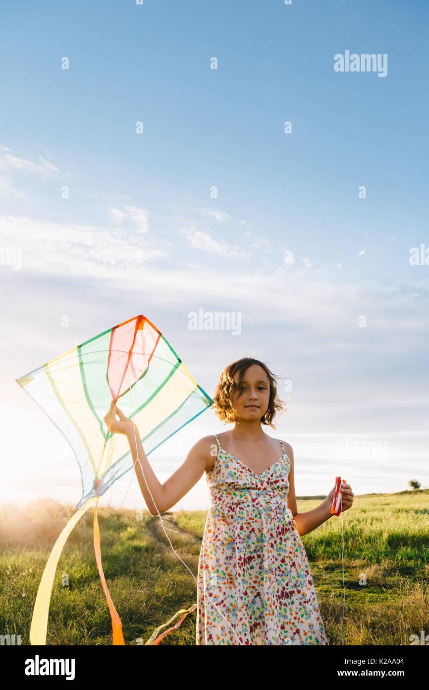 Chica sujetando el kite y se ejecuta en el campo Imagen De Stock