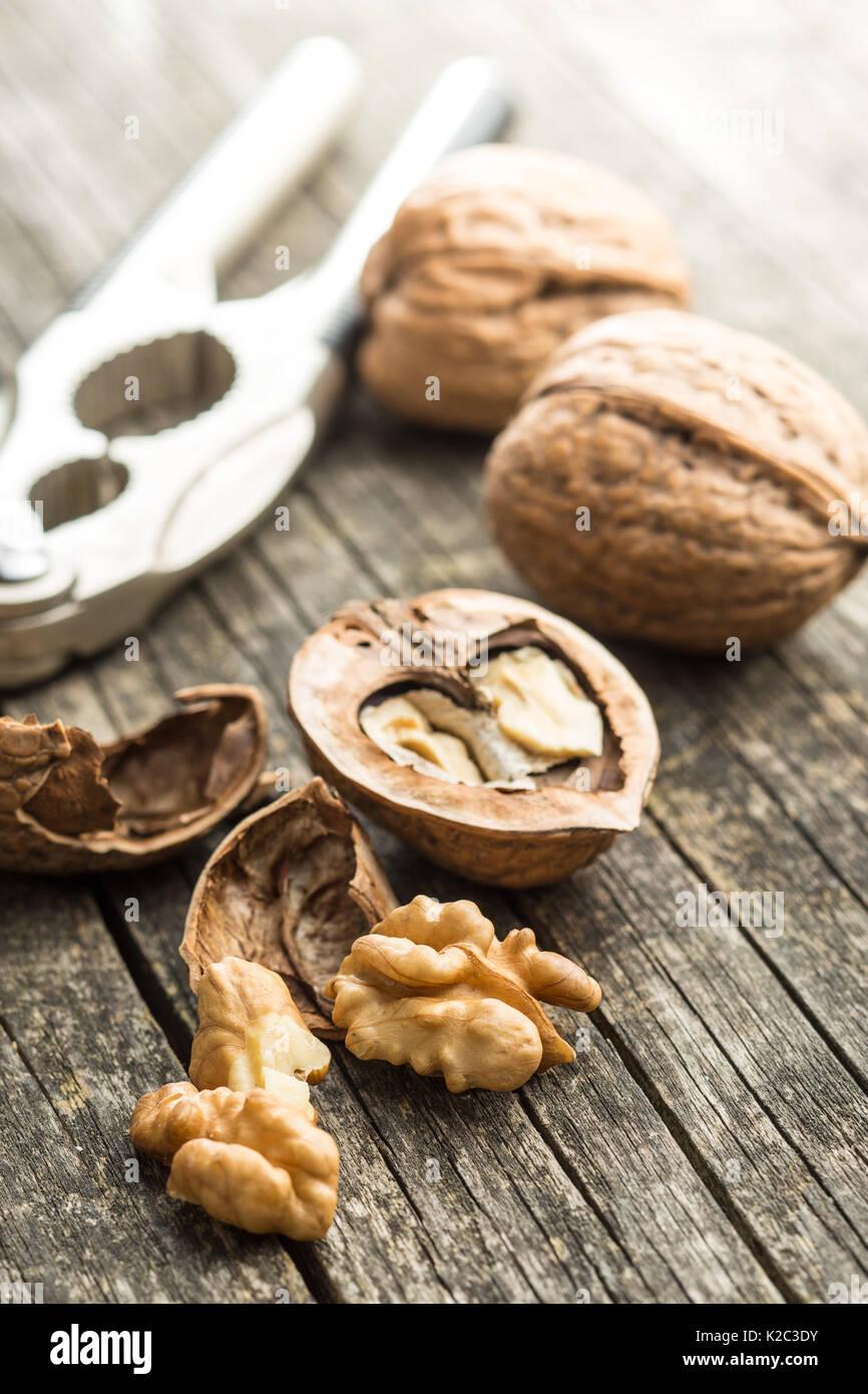 Nueces secas agrietado y cascanueces sobre mesa de madera antigua. Imagen De Stock
