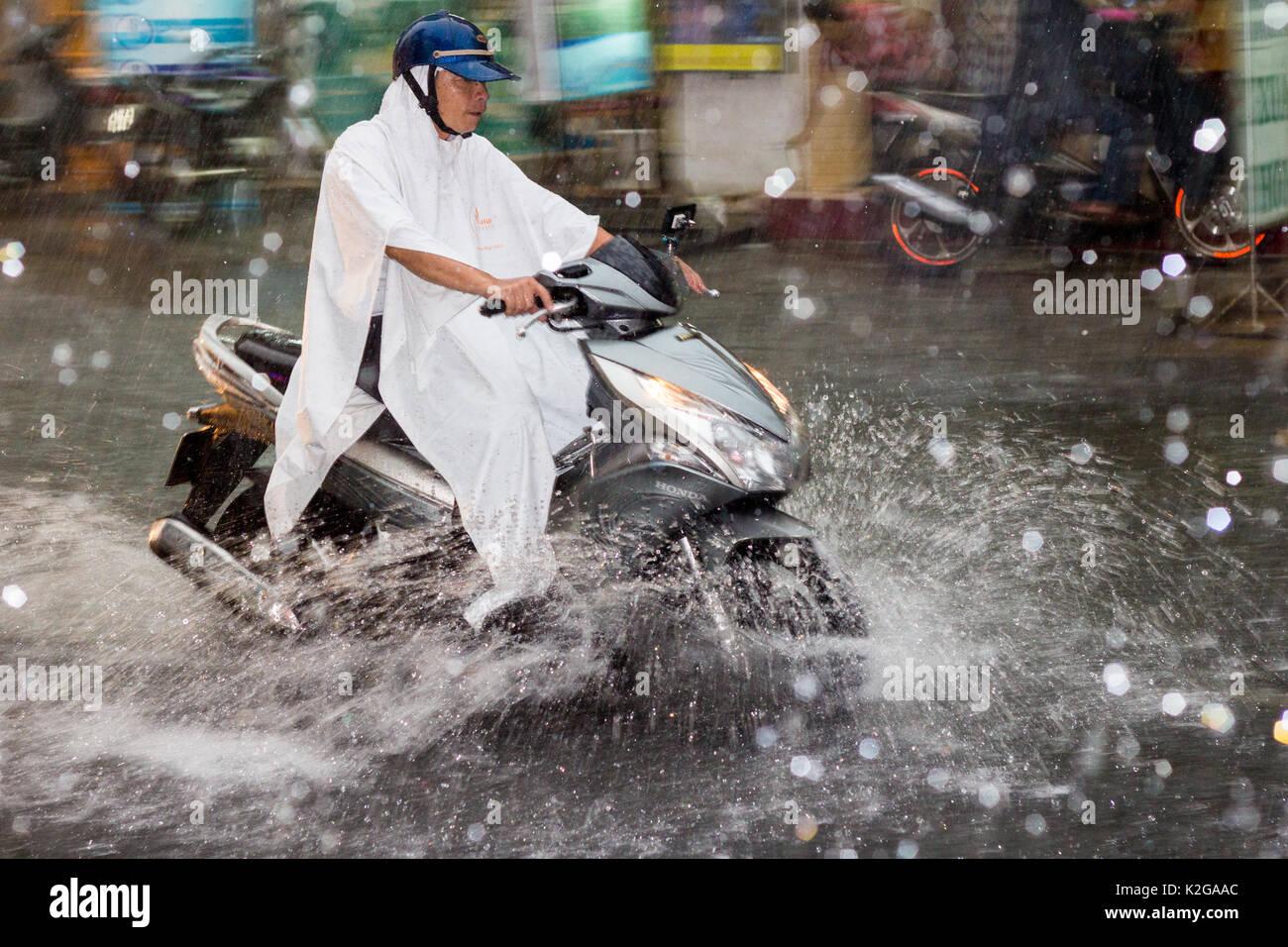 Hombre en moto duros a través de las inundaciones y lluvias torrenciales en la calle Bui Vien, Ciudad Ho Chi Minh (Saigón), Vietnam Imagen De Stock