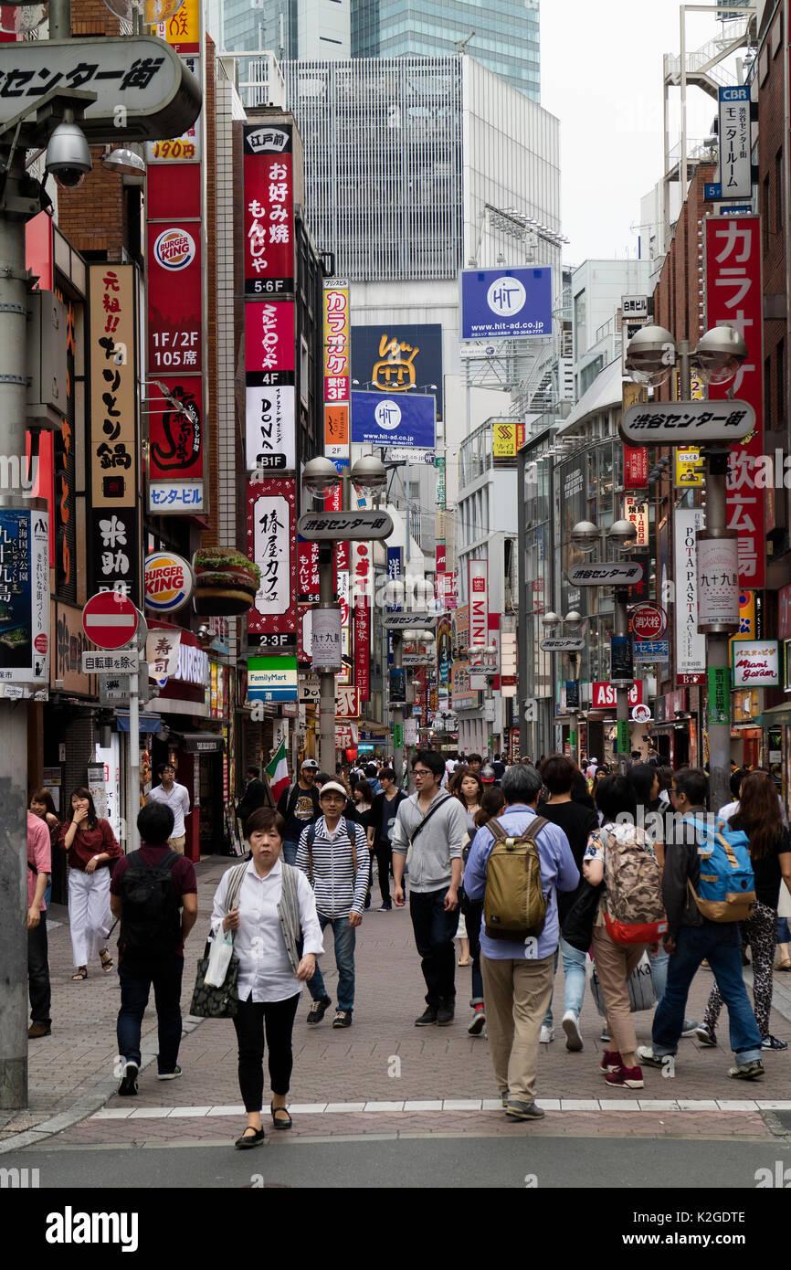 Tokio, Japón - El 12 de mayo de 2017: los peatones y signos de anuncio en la calle comercial de Shibuya Imagen De Stock