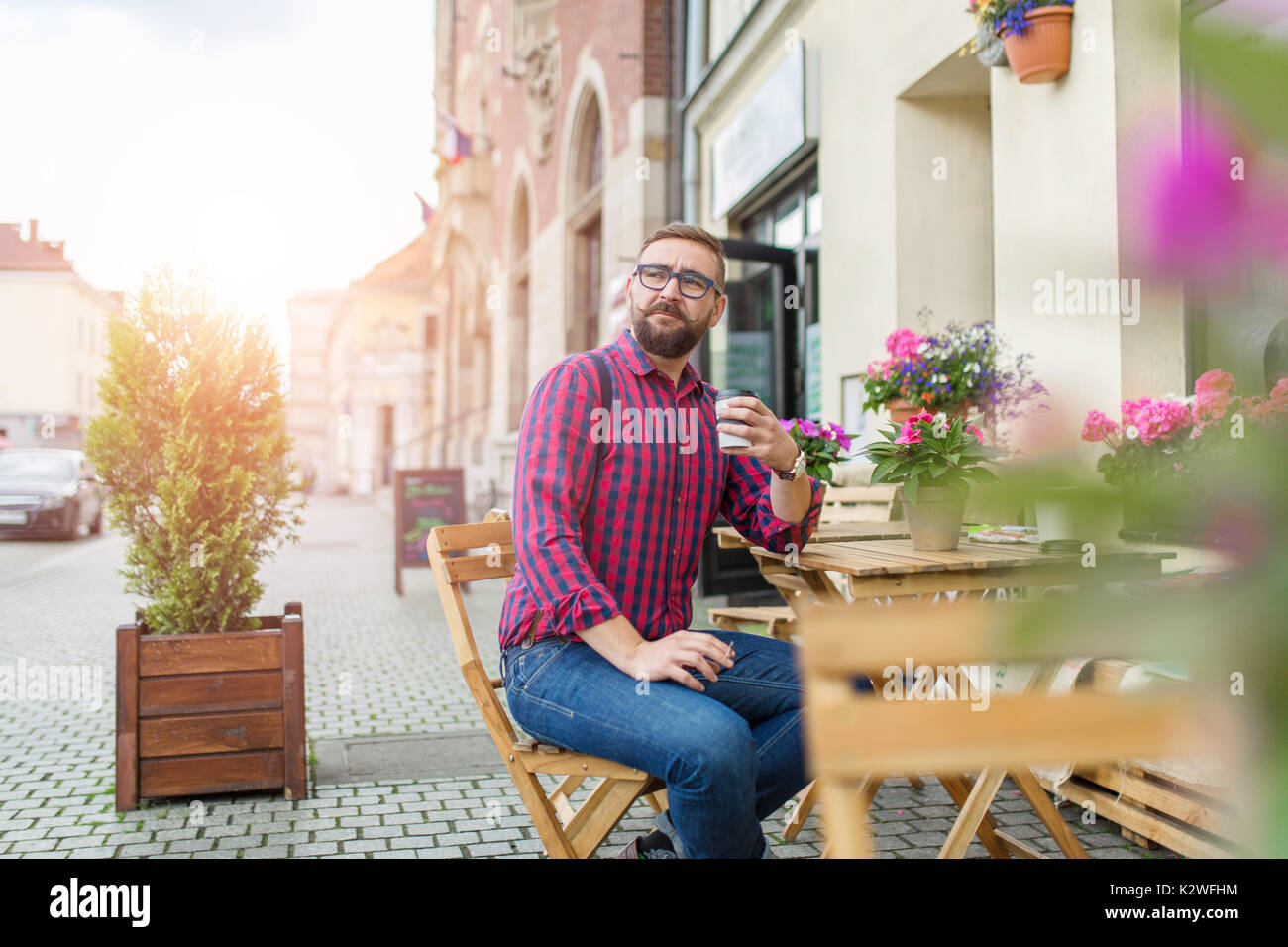 Hombre sentado en el café jardín y beber café para llevar Imagen De Stock