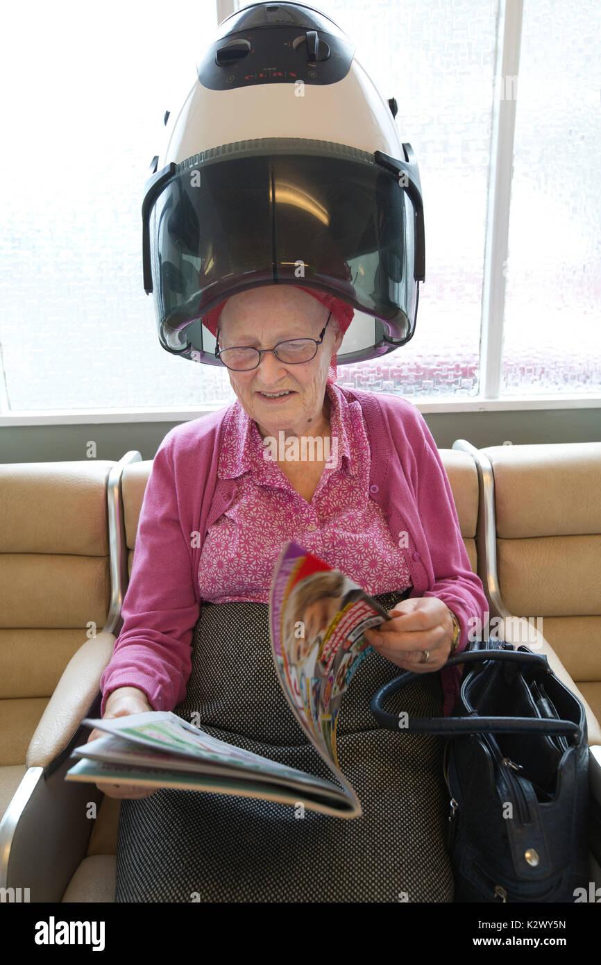 Jubilado anciano tener sus cabellos secos en una capucha de pelo rizadores de desgaste en un salón de peluquería para damas, England, Reino Unido Imagen De Stock