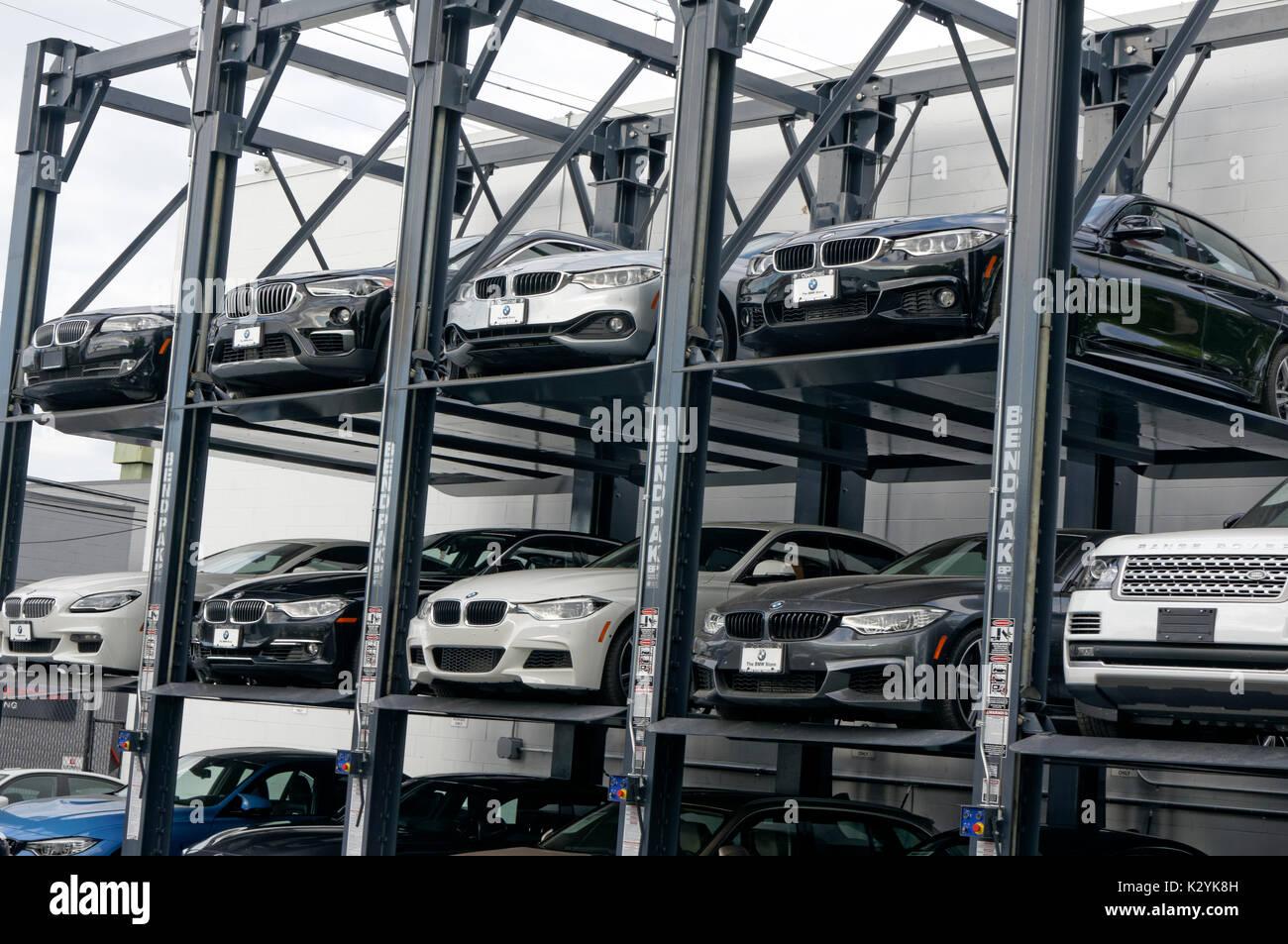 Nuevo lujo automóviles estacionados en un rack de los ascensores de varios niveles en la tienda de BMW concesionario en Vancouver, BC, Canadá Imagen De Stock