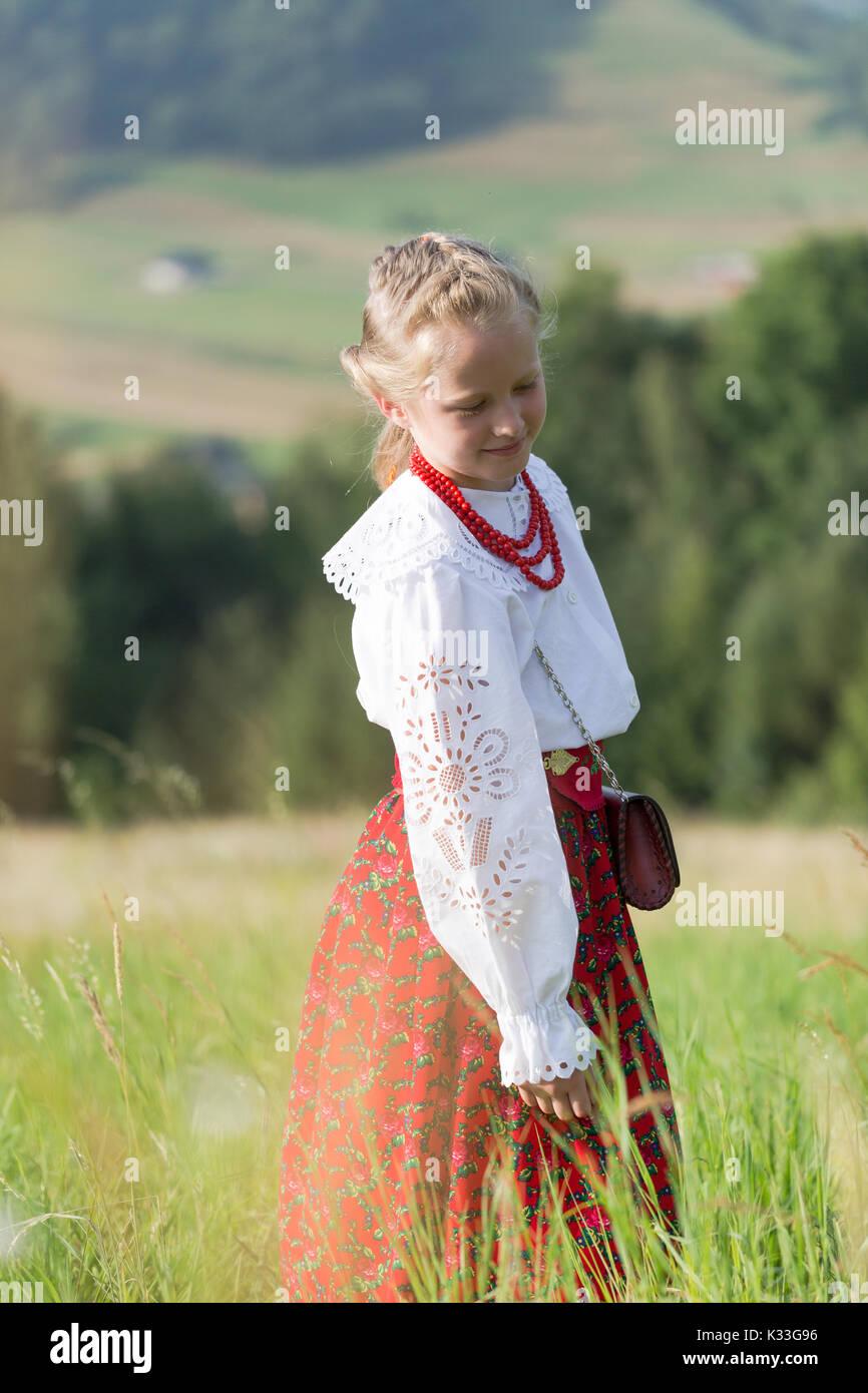 Chica polaca traditioal vestido de montaña se encuentra en el verde prado en las montañas. Cgild mirando hacia abajo a las flores. Retrato unposed vertical con shal Foto de stock