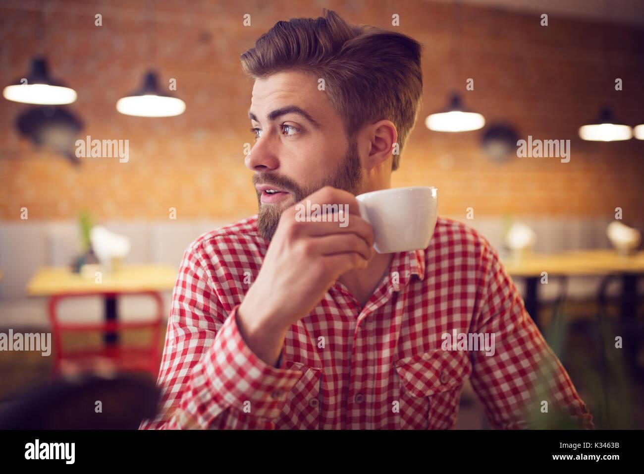 Una foto de joven en camisa de cuadros para sentarse en la cafetería con una taza de café en su mano. Imagen De Stock