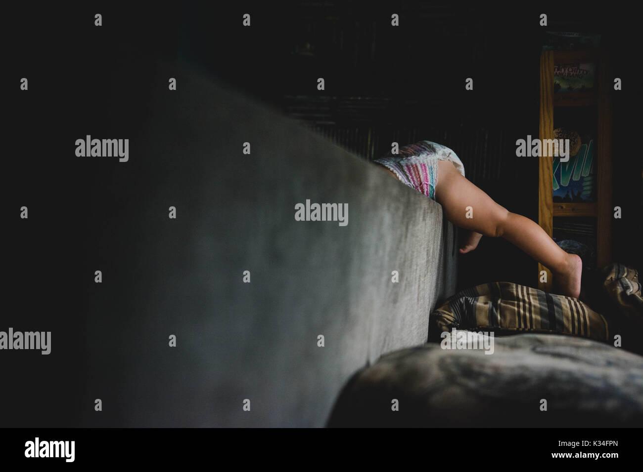 Un pañal clad toddler trepa sobre un sofá con sus piernas apareciendo Imagen De Stock
